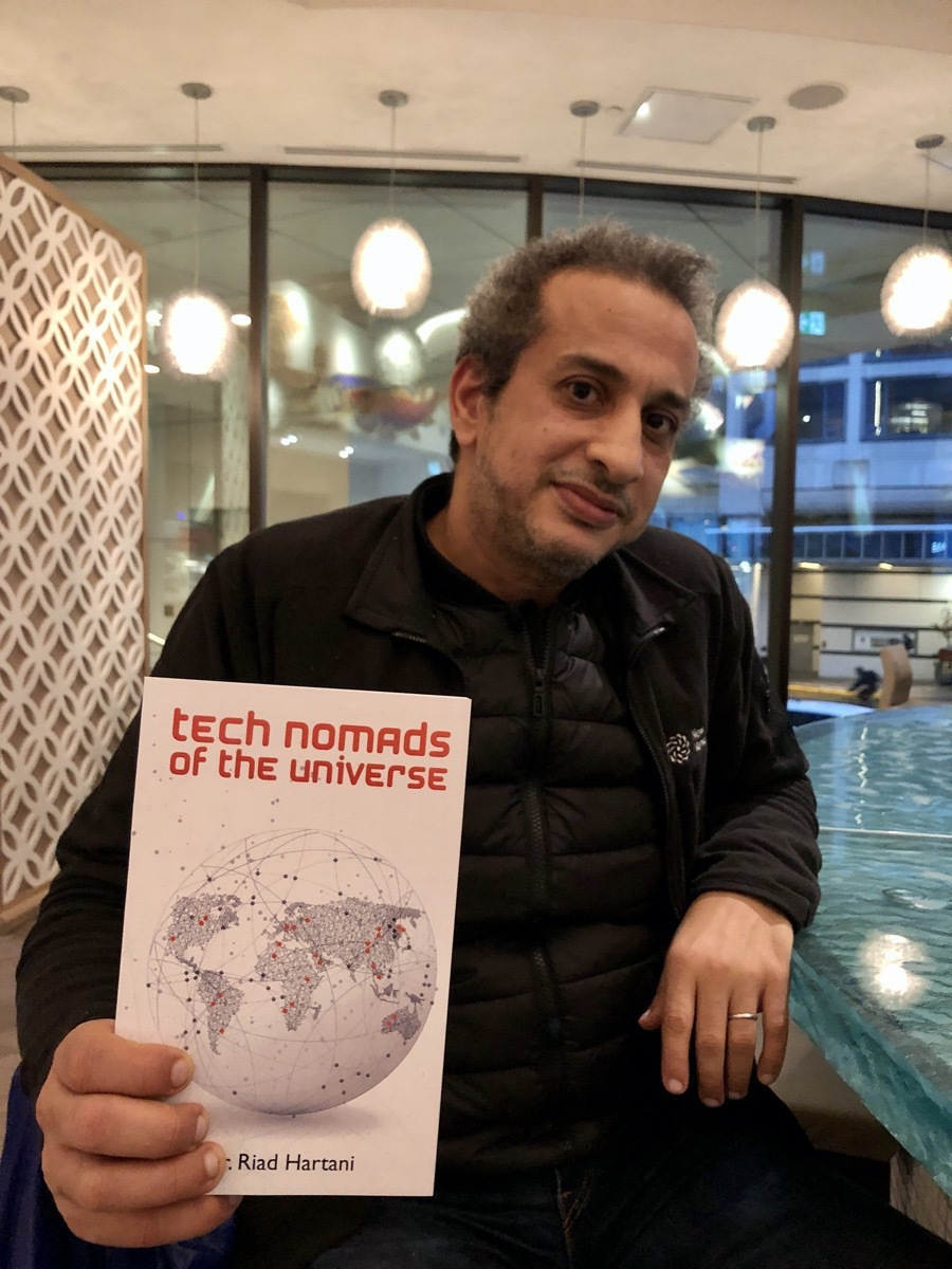 Riad Hartani holding Tech Nomads of the Universe book